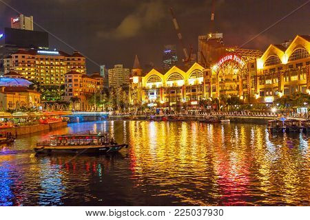 CLARKE QUAY, SINGAPORE - AUGUST 16, 2009: A traditional bumboat on the Singapore River at night, with Clarke Quay on the left and Riverside Point on the right.