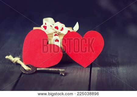 Red paper heart old key and presents on a dark wooden background. St. Valentine's Day. Copy space. Greeting card.
