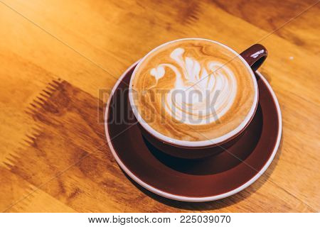Late hot offee with late art in cup on wood table
