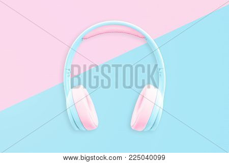 Colorful headphones on blue pink pastel background. Minimal fashion music concept