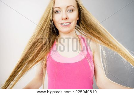 Haircare and hairstyling concept. Young woman touching her long blonde natural hair.