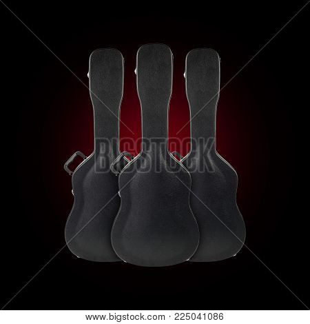 Musical instrument - Three black acoustic guitar hard case on a black background.