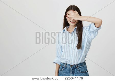Studio portrait of young and pretty young lady covering eyes with hands and smiling with excitement, waiting for something over gray background. Girl covers her eyes while her friend changes clothes.