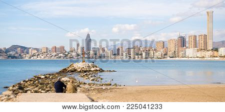 Couple eldery people sitting against sea and watching at Benidorm city.