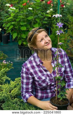 girl gardener looks at tall flower in a greenhouse