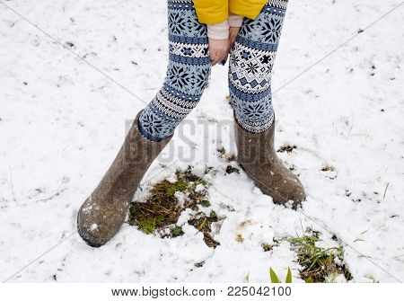 Maiden legs in warm pants and felt boots. The girl in the snow in the winter.