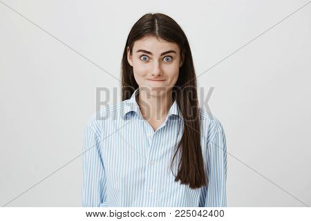 Indoor shot of funny caucasian model with tightened lips and widened eyes, standing over gray background. Woman looks childish while being puzzled and uncertain about decision she should make.