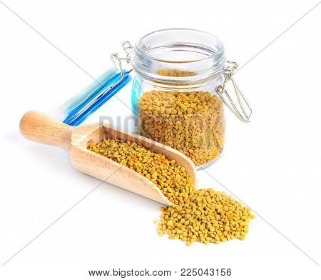 Bee pollen in a glass jar and a wooden shovel is isolated on a white background. Natural remedy for immunity enhancement. Beekeeping products
