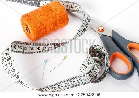 Accessories for sewing: thread, scissors, needle and centimetre on a white background. Orange bobbin of thread.
