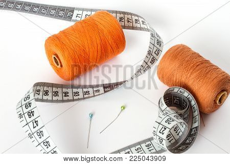 Accessories for sewing: thread, needle and centimetre on a white background. Orange bobbin of thread and brown.