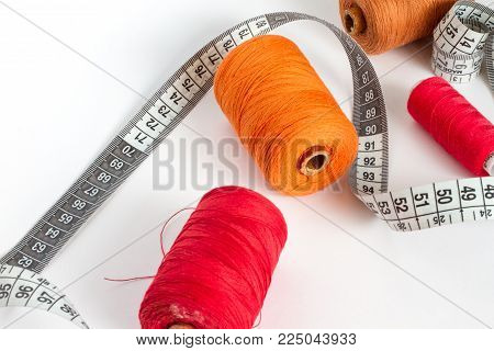 Accessories for sewing: thread, needle and centimetre on a white background. Orange, brown and red bobbin thread.