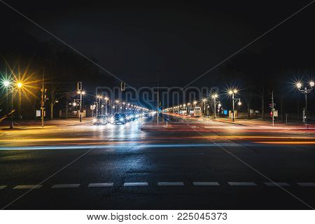Long city road with light trails at night. Long exposure photo of straight wide road in Berlin
