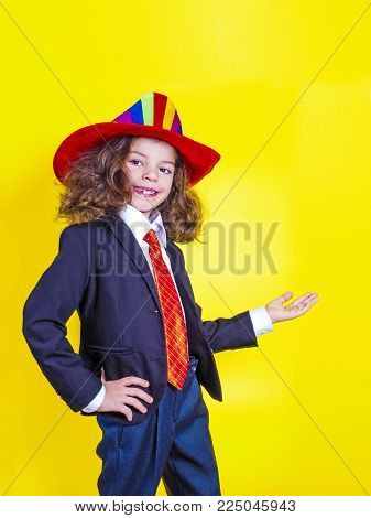 Look here. Side view of a surprised cute little businessman stands in pointing his hand, looking into the camera with curiosity and a smile. Yellow background