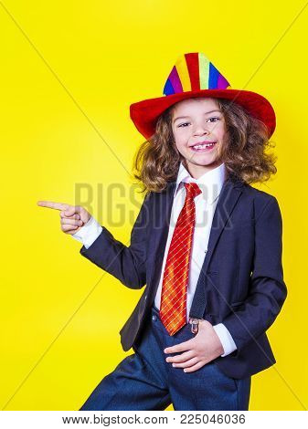 Look here. Side view of a surprised cute little businessman stands in pointing his finger, looking into the camera with curiosity and a smile. Yellow background
