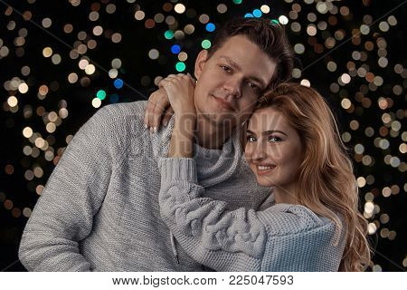 Beautiful woman hugging her boyfriend looking happy to camera with lights in background. Happy man and woman portrait wearing same color clothes. Low light