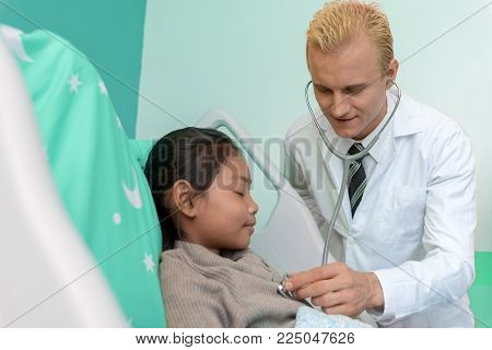 Doctor checking and analysis pulse of the heart from young patient in bed room ward. Healthcare and Hospital concept. Happiness life and insurance theme. Kids and Children theme.