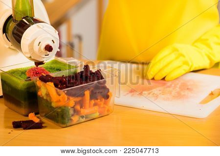 Woman hands adding different vegetables red and green in juicer maker. Housewife in kitchen making raw juice, preparing nutritious vitamin packed drink. Healthy eating, vegetarian food, dieting.