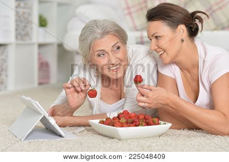 Mother and her adult daughter looking at tablet while eating fresh strawberries