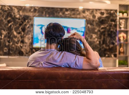 Asian young lovers watching television on sofa. Couples and Relax concept. Holiday and vacation concept. Night dating and honeymoon theme. Back view