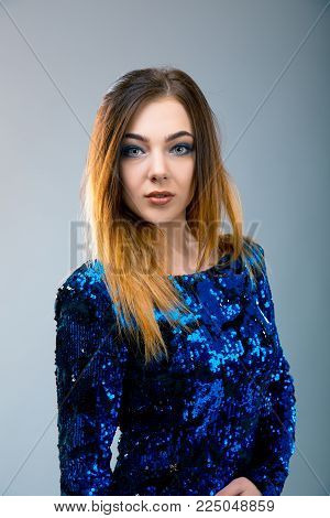Ladylike woman in the blue evening sparkling dress is posing over grey background. Model test