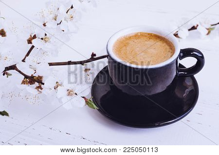Espresso and cherry blossom background. A cup of coffee and tree's branch with flowers on shabby chic wooden table. Breakfast on Women's, Valentine's or Mother's day. Spring morning concept.