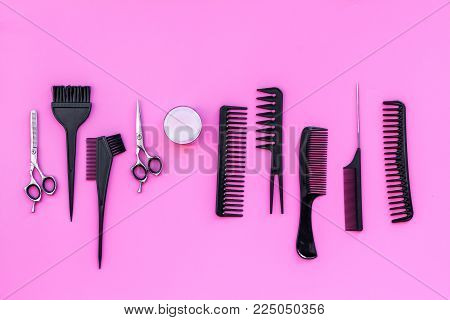 Beauty saloon equipment. Hairdress and haircut. Combs, sciccors, brushes on pink background top view.