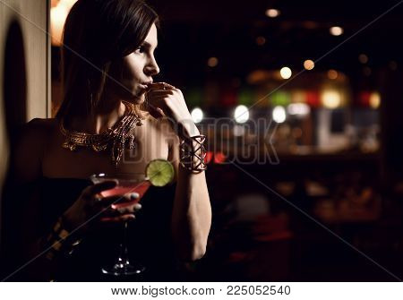 Beautiful sexy fashion brunette woman in expensive interior restaurant drink martini cosmopolitan cocktail on dark cafe background