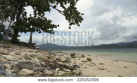 Wild beautiful beach with sand and coconut palms. Tropical bay in El Nido. Sky and mountains rocks. . Seascape: mountains, ocean., beach. Philippines, El Nido Travel concept