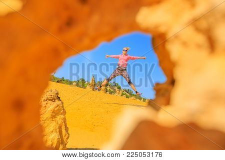 View of a young happy caucasian woman jumping through an eroded limestone pillars of Pinnacles Desert, Nambung National Park, Cervantes, West Australia. Australia travel freedom concept.