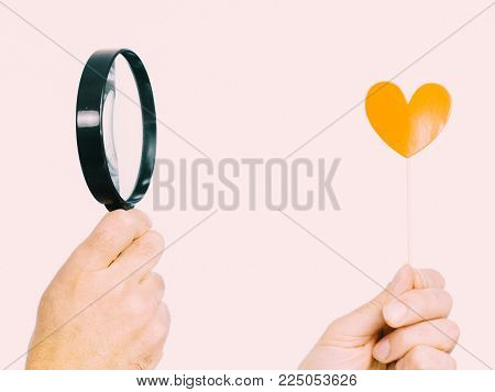 Uncertain person looking at love little heart shape on stick using magnifying glass. Studio shot