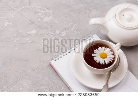 White porcelain cup of black tea with chamomile flowers on grey stone background. Copy space. Healthy lifestyle concept.