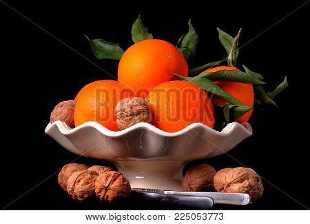 Ceramica con  arance e noci su fondo nero