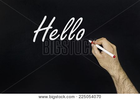 chalk drawing concept 2018. Person's hand drawing with chalk on blackboard the word: HELLO