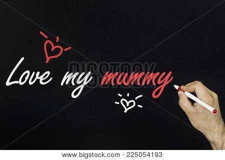 Person's hand drawing with chalk on blackboard - Love you mummy