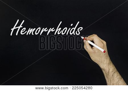 chalk drawing concept 2018. hemorrhoids treatment. Person's hand drawing with chalk on blackboard.