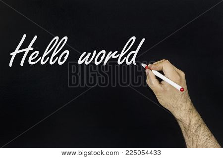 chalk drawing concept 2018. Person's hand drawing with chalk on blackboard the word: HELLO World