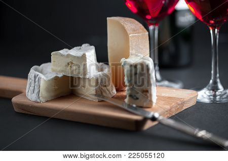 Assortment of cheeses  on a wooden plate with vintage silver knife and two glasses of red wine. Horisontal.