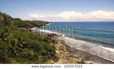 Rocky beach with palm trees, blue water on a tropical island. Sea rocky coast, waves breaking to the rocky shore. Viewpoint along stony beach with rocks.Stony sea beach scene. Philippines. Travel concept.