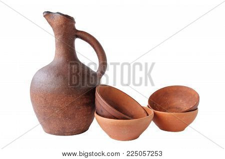 Terracotta clay jug and a few wine cups on a white background, isolated