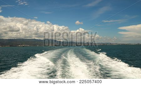 Water trace formed from powerful speed ferry engines, cruising at high speed. Trail on sea surface behind of speed boats. Water trail foaming behind a ferry. Travel concept.