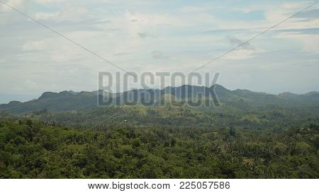 Vew Mountains with rainforest covered with green vegetation and trees on the tropical island, landscape. Mountains and hills with wild forest, sky clouds. Hillside rainforest and jungle. Philippines, Bohol .