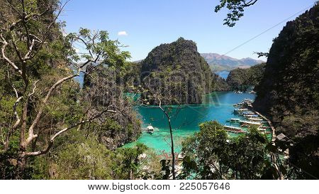 Tropical lagoon with azure water, beach by the Kayangan Lake, Philippines. View Coron island, with cove, bay at Kayangan lake. Lagoon with sailing boats. Philippines. Travel concept