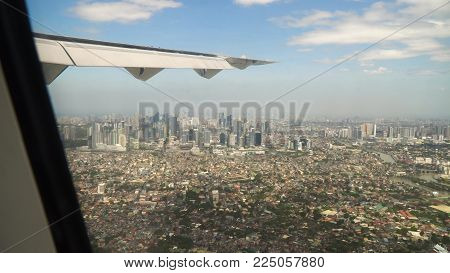 View through an airplane window on the city. Airplane window view showing wing of a plane flying over Manila. Aerial footage, Philippines. Travel concept.