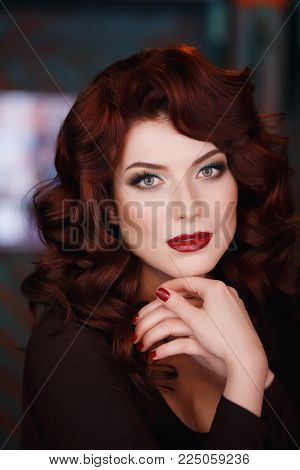 Portrait of beautiful redhead young girl with red lipstick. Concept person for glossy magazine, model. looks into the frame.
