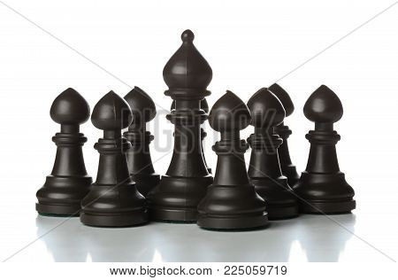 Runner chess figure standing in between pawn chess figures - management, leadership, teamlead or strategy concept over white background
