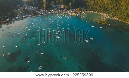 Aerial view of sailing boats and yachts in the bay. Boat and yacht in the tropical lagoon. Aerial view: tropical landscape. Tropical island. Philippines, El Nido. Travel concept.