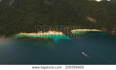 Beautiful beach with boats and tourists. Tropical bay in El Nido. Aerial view: bay and the tropical island. Tropical lagoon with turquoise water and white sand. Seascape: mountains, ocean. Philippines, El Nido. Travel concept.