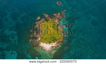 Aerial view of beautiful tropical island with sand beach, El Nido. Tropical lagoon with turquoise water and yellow sand. Seascape: Ocean and a beautiful beach paradise. Beautiful view of a nice tropical beach from the air. Philippines. Travel concept.