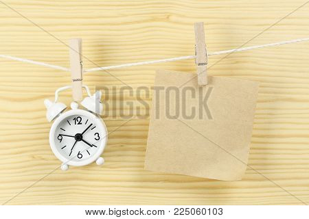 clock and blank note on clothesline for your text