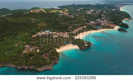 Aerial view of beautiful tropical island with white sand beach, Boracay, hotels and tourists. Tropical lagoon with turquoise water and white sand. Beautiful sky, sea, beach, resort. Seascape: Ocean and beautiful beach paradise..